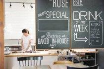 Mulher em um balcão de trabalho em uma padaria . — Fotografia de Stock