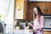 Senior woman standing in a kitchen — Stock Photo