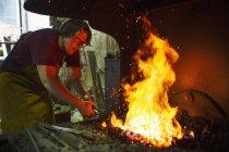 Blacksmith heats something in a furnace. — Stock Photo