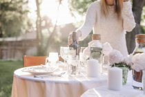 Frau einrichten einen Tisch in einem Garten — Stockfoto