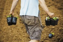Man walking carrying plant pots — Stock Photo