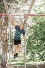 Ragazzo sulla struttura nel giardino d'arrampicata — Foto stock