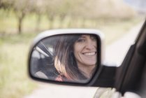 Woman in a car, smiling — Stock Photo