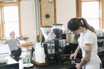 Donna davanti alla macchina da caffè espresso — Foto stock