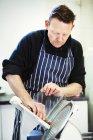 Metzger schneidet Salami mit Aufschnittmaschine — Stockfoto