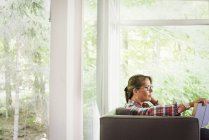 Woman sitting on a sofa reading a book. — Stock Photo