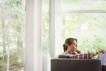 Frau sitzt auf einem Sofa und liest ein Buch. — Stockfoto
