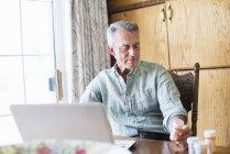 Старший чоловік за допомогою портативного комп'ютера — стокове фото