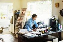 Donna che lavora alla scrivania in studio interno — Foto stock