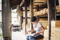 Frau hält Ordner in der Hand und macht Notizen — Stockfoto