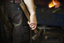 Homem segurando um martelo em uma oficina . — Fotografia de Stock