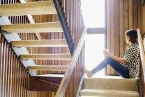 Femme assise sur un escalier en bois — Photo de stock
