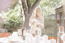 Woman setting a table in a garden — Stock Photo
