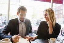 Femme d'affaires et homme d'affaires assis à table à café — Photo de stock