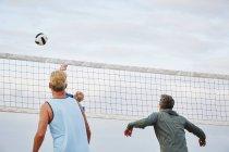 Mature men playing beach volleyball. — Stock Photo