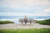 Жінка, сидячи на пляжі на березі океану — стокове фото