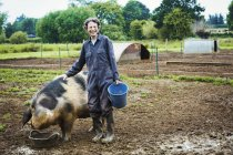 Woman standing by large pig — Stock Photo