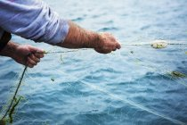 Fisherman pulling the net out of the water. — Stock Photo