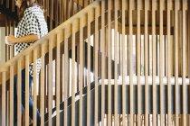 Женщина спускается по деревянной лестнице . — стоковое фото