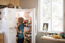 Boy standing at open fridge — Stock Photo