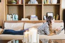 Donna sdraiata su un divano, leggendo un libro . — Foto stock