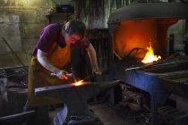 Herrero golpeando rojo caliente metal - foto de stock