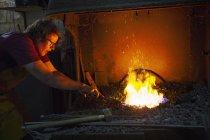Blacksmith using tongs — Stock Photo