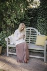 Woman sitting in a garden on a bench — Stock Photo