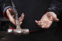 Forgeron tenant un marteau métallique . — Photo de stock