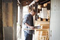 Mann hält Ordner in der Hand und kontrolliert Holz — Stockfoto