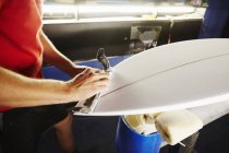 Man working on a surfboard in a workshop. — Stock Photo