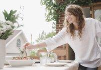 Mulher em pé ao lado de uma mesa — Fotografia de Stock