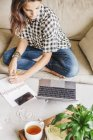 Woman on a sofa with a laptop computer — Stock Photo