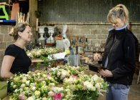 Florists at workbench covered in table decorations — Stock Photo