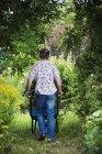 Mulher empurrando carrinho de mão de jardim — Fotografia de Stock
