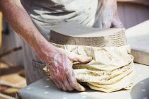 Woman potter unwrapping a bag of clay — Stock Photo