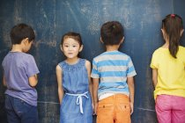 Four children standing by the blackboard. — Stock Photo