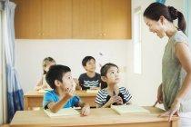 Niños en un aula con profesor - foto de stock