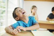 Niño sentado en un aula y riendo - foto de stock
