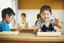 Niños trabajando juntos en un aula - foto de stock