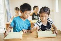 Bambini che lavorano insieme in un'aula — Foto stock
