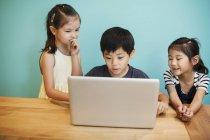 Enfants à l'école avec ordinateur portable — Photo de stock