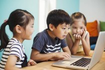 Three children using a laptop — Stock Photo