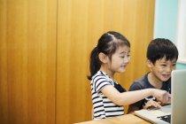 Children sharing a laptop computer. — Stock Photo