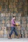 Uomo che trasporta una cassa vuota . — Foto stock