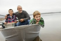 Man and boys fishing from a boat. — Stock Photo