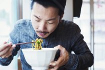Man eating ramen noodles — Stock Photo