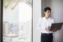 Geschäftsmann mit seinem Laptop durch Fenster — Stockfoto