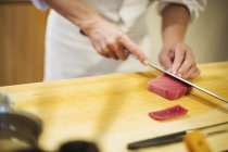 Chef slicing fish for making sushi — Stock Photo