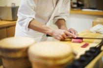 Schneiden von Fisch für die Herstellung von Sushi Koch — Stockfoto
